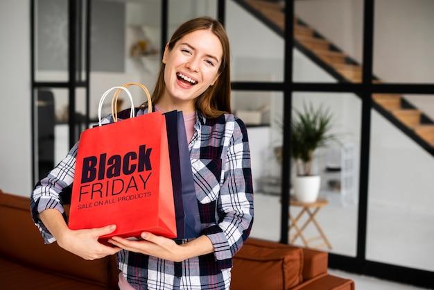 Vrouw die zwarte vrijdag papieren zakken draagt