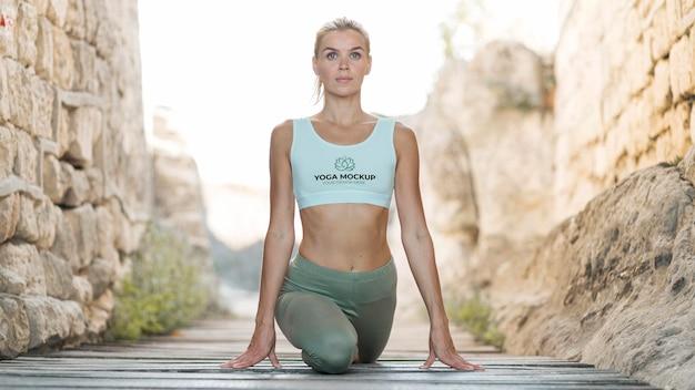 Vrouw doet yoga terwijl ze een mock-up sportbeha draagt