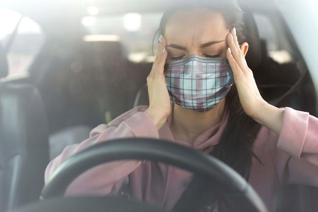 Vrouw in auto die hoofdpijn ervaart
