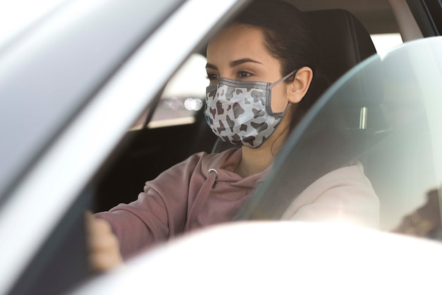 Vrouw in auto die masker draagt