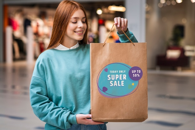 Vrouw in een winkelcentrum met een grote papieren zak gevuld met producten te koop