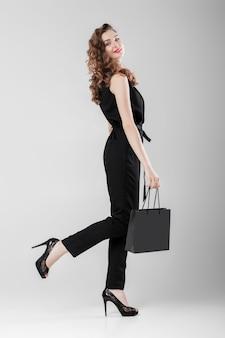 Vrouw in het zwart met boodschappentas.