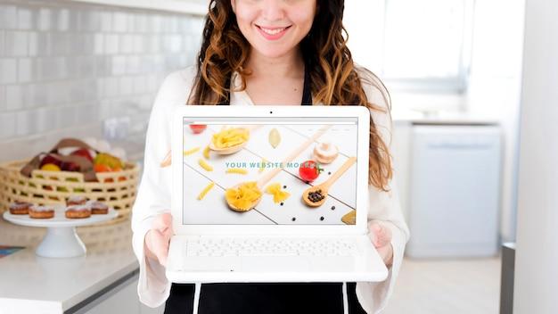 Vrouw in keuken die laptop model voorstelt