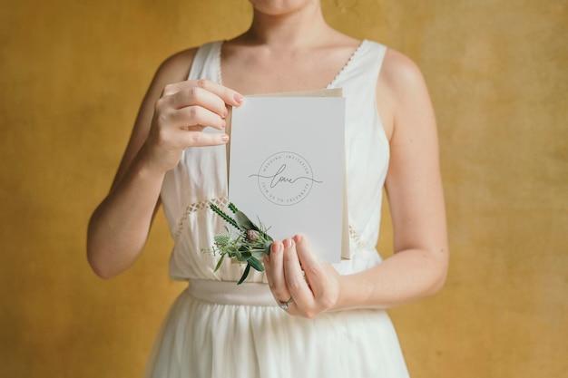 Vrouw met een mockup voor een huwelijksuitnodiging