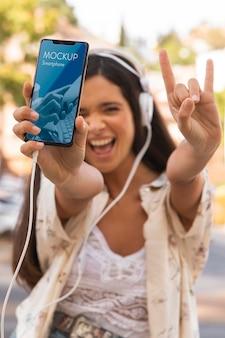 Vrouw met smartphone en luisteren naar muziek op de koptelefoon