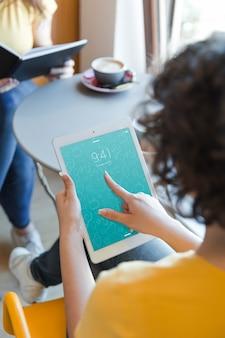 Vrouw met tablet in bibliotheek