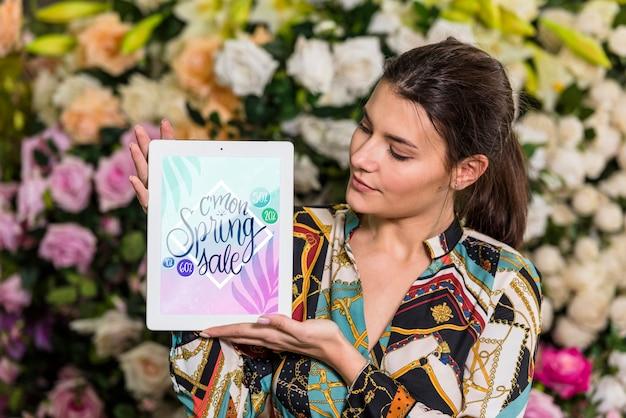 Vrouw met tablet mockup voor lente verkoop