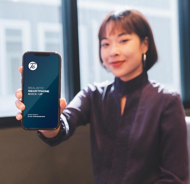 Vrouw toont haar smartphone scherm mockup in café