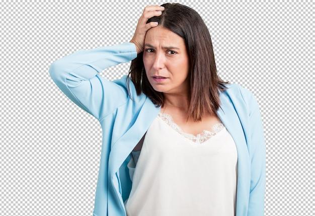 Vrouw van middelbare leeftijd bezorgd en overweldigd, vergeetachtig, realiseer zich iets, uitdrukking van shock omdat ze een fout heeft gemaakt
