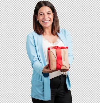 Vrouw van middelbare leeftijd blij en lachend, houdt een leuke gave, opgewonden en vol, viert een verjaardag of een uitgelichte evenement