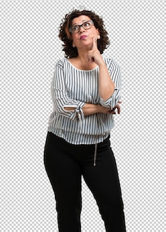 Vrouw van middelbare leeftijd die denkt en opkijkt, verward over een idee, zou proberen een oplossing te vinden
