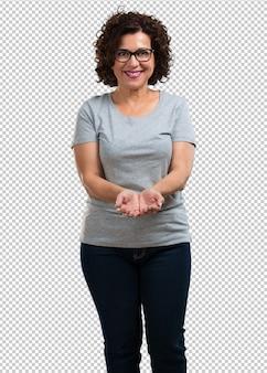 Vrouw van middelbare leeftijd die iets met handen houdt, een product toont, glimlachend en vrolijk, met een denkbeeldig object