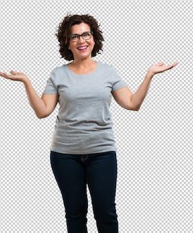 Vrouw van middelbare leeftijd die lacht en plezier maakt, ontspannen en vrolijk is, voelt zich zelfverzekerd en succesvol