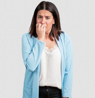 Vrouw van middelbare leeftijd die nagels bijt, nerveus en erg angstig en bang voor de toekomst, voelt paniek en stress