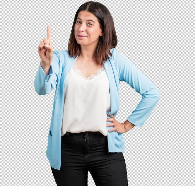 Vrouw van middelbare leeftijd die nummer één, symbool van het tellen, van wiskunde, zelfverzekerd en vrolijk toont