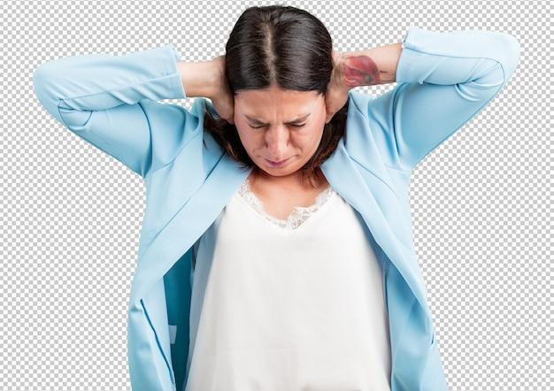 Vrouw van middelbare leeftijd die oren bedekt met handen, boos en moe van het horen van wat geluid