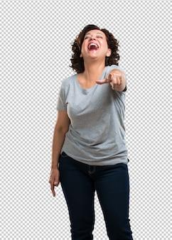 Vrouw van middelbare leeftijd die schreeuwt, lacht en grappen maakt over een ander, over spot en ongecontroleerd