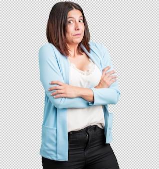 Vrouw van middelbare leeftijd die twijfelt en haar schouders ophaalt, concept van besluiteloosheid en onzekerheid, onzeker over iets