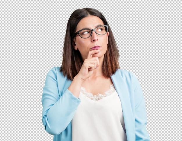 Vrouw van middelbare leeftijd die twijfelt en verward is, een idee bedenkt of zich ergens zorgen over maakt