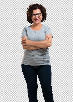 Vrouw van middelbare leeftijd die zijn armen kruist, glimlachend en gelukkig, zelfverzekerd en vriendelijk