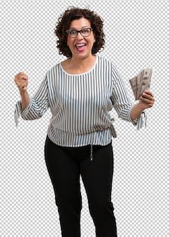 Vrouw van middelbare leeftijd erg opgewonden en euforisch, schreeuwend vooruit kijkend, een overwinning en een succes vieren nadat ze de loterij heeft gewonnen, bankbiljetten met hand vasthouden, concept van geluk