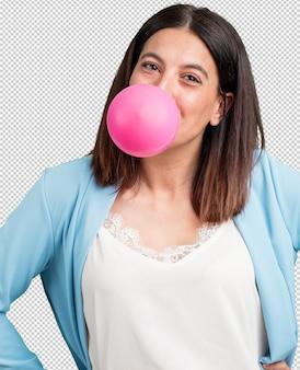 Vrouw van middelbare leeftijd gelukkig en blij, inclusief een kauwgomballon, zeer speels en lief, leuk concept