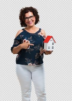 Vrouw van middelbare leeftijd gelukkig en zelfverzekerd, toont een miniatuur huismodel, probeert het te verkopen, thuis en familie
