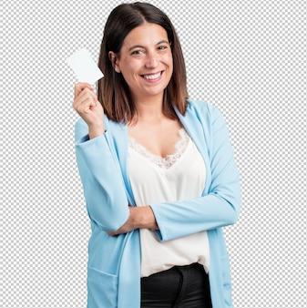 Vrouw van middelbare leeftijd lacht zelfverzekerd, biedt een visitekaartje aan, heeft een bloeiend bedrijf, kopieer ruimte om te schrijven wat je maar wilt