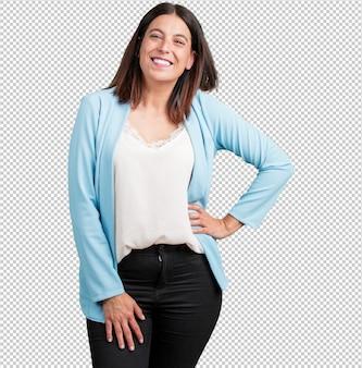 Vrouw van middelbare leeftijd met handen op de heupen, permanent, ontspannen en glimlachend, zeer positief en vrolijk