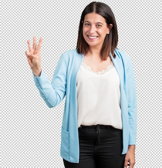 Vrouw van middelbare leeftijd met nummer drie, symbool van tellen, wiskunde, zelfverzekerd en vrolijk