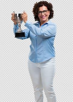 Vrouw van middelbare leeftijd opgewonden en energiek, een glas heffen na het behalen van een moeilijke overwinning, beloning voor hard werken, zelfverzekerd en positief