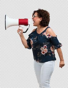 Vrouw van middelbare leeftijd opgewonden en euforisch, schreeuwend met een megafoon, teken van revolutie en verandering, aanmoedigend andere mensen om te bewegen, leider persoonlijkheid