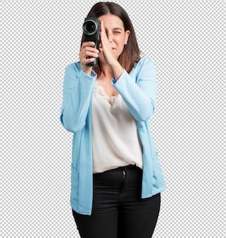 Vrouw van middelbare leeftijd opgewonden en vermaakt, kijkend door een filmcamera, op zoek naar een interessant schot, een film opnemen, uitvoerend producent