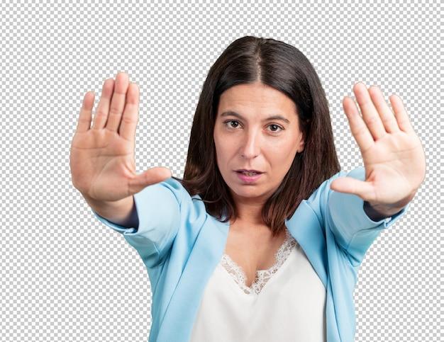 Vrouw van middelbare leeftijd serieus en vastberaden, hand in hand, stop gebaar, ontkennen concept