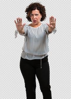 Vrouw van middelbare leeftijd serieus en vastberaden, hand in hand, stop gebaar, ontkennen