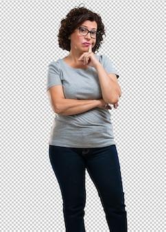 Vrouw van middelbare leeftijd twijfelt en verward, denkend aan een idee of bezorgd over iets