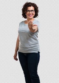 Vrouw van middelbare leeftijd uit te nodigen om te komen, zelfverzekerd en lacht het maken van een gebaar met de hand, wordt positief en vriendelijk