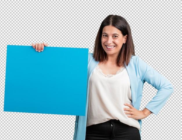 Vrouw van middelbare leeftijd vrolijk en gemotiveerd, met een lege poster waar u een bericht, communicatie kunt tonen