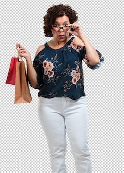 Vrouw van middelbare leeftijd vrolijk en glimlachend, erg opgewonden met een boodschappentas, klaar om te gaan winkelen en op zoek te gaan naar nieuwe aanbiedingen