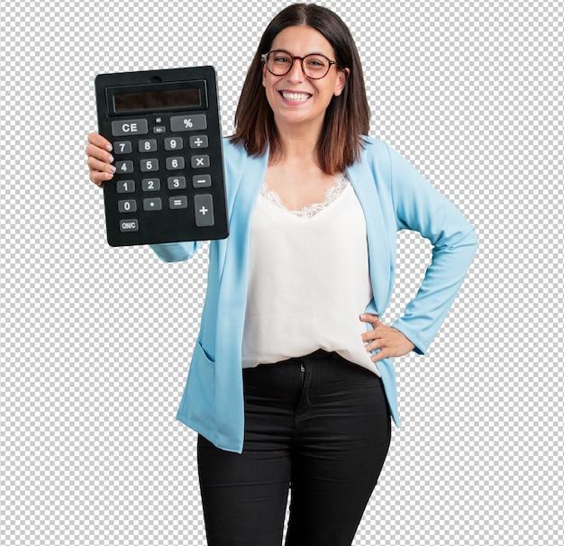 Vrouw van middelbare leeftijd vrolijk en glimlachend, met een rekenmachine, exacte berekeningen, gegevensinformatie