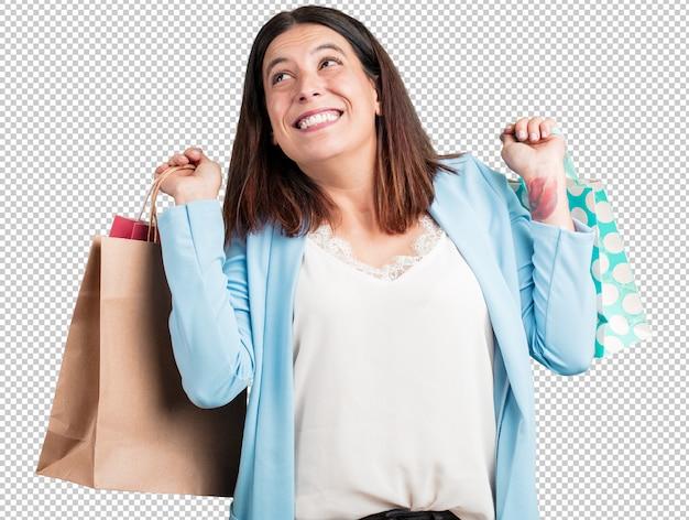 Vrouw van middelbare leeftijd, vrolijk en lachend, zeer enthousiast met een boodschappentas