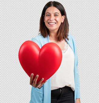 Vrouw van middelbare leeftijd vrolijk en zelfverzekerd, met een hartvorm aan de voorkant, concept van liefde, gezelschap en vriendschap