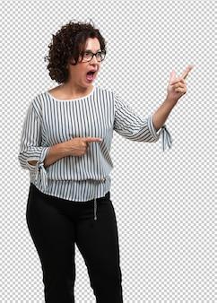 Vrouw van middelbare leeftijd wijst naar de kant, glimlachend verrast presenteren iets, natuurlijk en casual