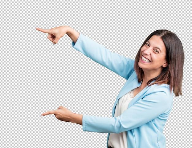 Vrouw van middelbare leeftijd wijzend naar de kant, glimlachend verrast iets presenteert, natuurlijke en casual