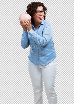Vrouw van middelbare leeftijd zelfverzekerd en opgewekt, met een biggenbank en stil omdat het geld wordt bespaard.