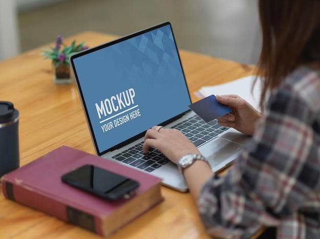 Vrouw winkelen en online betalen met creditcard op laptopmodel