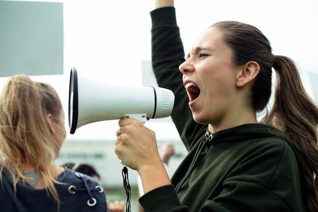 Vrouwelijke activist die op een megafoon schreeuwt