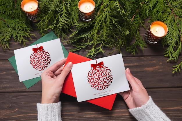 Vrouwelijke handen houden een kerstkaart en een envelop mockup voor kersttijd vast