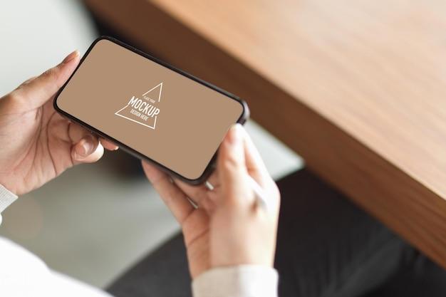 Vrouwelijke handen met smartphone met wit scherm voor reclameweergave en onscherpe achtergrond