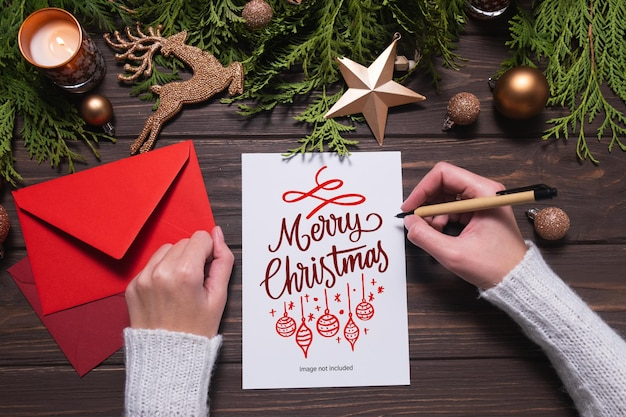 Vrouwelijke handen schrijven kerstkaart of brief op houten tafel met sparren en versieringen. mockup
